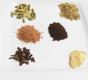 Clockwise from top left: green cardamom pods; fennel seeds; ginger; cloves. Center: cacao powder; Assam tea.